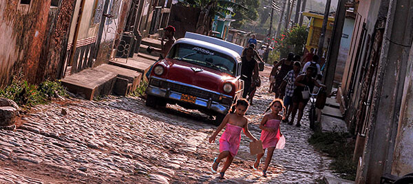 Girls running down the street and an old car in Cuba