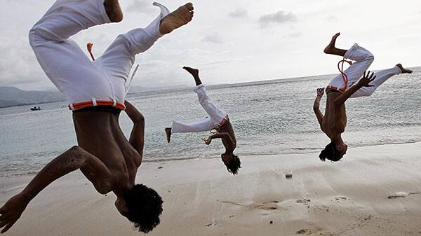 Practicing Capoeira moves on the beach