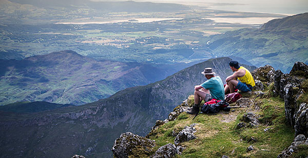 Resting hikers on mountaintop in Wales