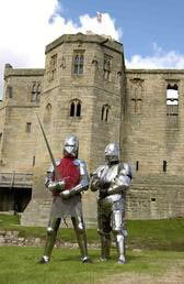 Two knights in armor outside Warkworth Castle