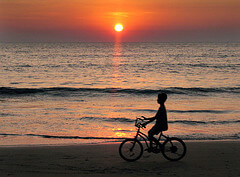 A boy on a bicycle at sunset