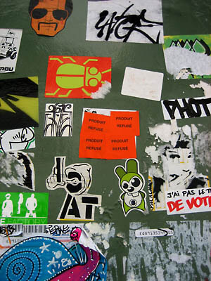 A bunch of cool stickers on a wall in Paris.