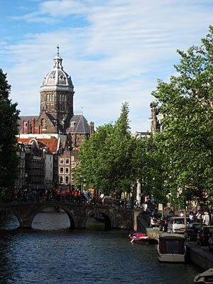 View over a canal in Amsterdam with an old church in the background.