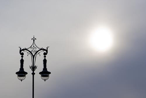Graphic shot of an ornate lamp post against a cloudy sky in Berlin.