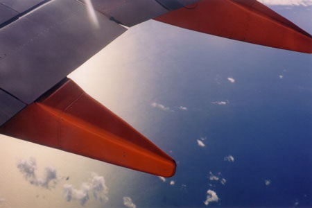 Dramatic red of the plane's wing contrasted to the white and blue of clouds and sea.